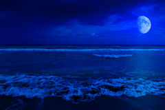 Night scene in a deserted beach. With a crescent moon stock photos