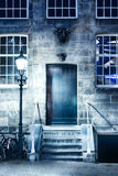 Night scene with a door and a light poll Stock Image