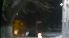 Night scene with falling snowflakes on blurred background of city.  stock footage