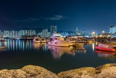 Night scene of Fishing village a small community with fishing boats and night cityscape at Lei Yue Mun water bay. Hong Kong royalty free stock photography