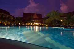 Night scene in hotel with purple sky. And swimming pool Royalty Free Stock Photography