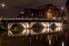 Night scene with lit bridge over a river with long reflections. Night scene with lit bridge over a still river with long reflections in a residential area with Royalty Free Stock Photo