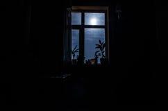 Night scene of moon seen through the window from dark room Stock Images