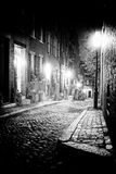 Night scene in old boston massachusetts. Black and white night image of an old 19th Century cobble stone road in Boston Massachusetts, Lit only by the gas lamps Stock Photos