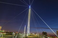 Night scene of Omaha Kerrey suspension bridge tower with suspension cables with beautiful sky colors just after sunset. Omaha Nebraska skyline with beautiful royalty free stock photo