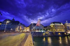 Night scene plus lightning in the sky of Basel on Mittlere Brucke stone bridge with Eisengasse road ahead. This image was taken atop of Rhine River with passerby Royalty Free Stock Photos
