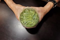 Top view a male hands holding a glass of iced matcha green tea on wooden dinning table royalty free stock photography