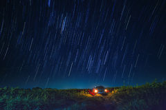 Night scene of star tail and blue sky over car parking in agriculture field royalty free stock photography