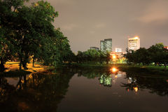 Night scene of State Railway Public Park. Also called  Suan Rot Fai, against modern buildings at twilight with reflection on the pond in Bangkok, Thailand Stock Image