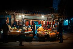 Night scene on the streets of Tbilisi, Georgia. Street sellers around corner selling traditional Georgian products with customers royalty free stock photography