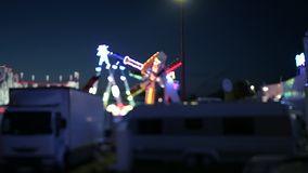 Night scene tilt-shift at dusk amusement park. Cinematic night scene of amusement park with parked white trucks and Ferris wheel merry-go-round spinning in the stock video footage