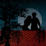 Night scene with two lovers. Sitting on the wall in front of the shining moon Royalty Free Stock Photography