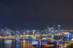 Night scenery of Da Nang city, Vietnam with the magic of light from the bridges, buildings and daydreaming. Of the river flowing to the sea. Artwork done royalty free stock photography