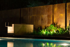 Night scenery near the poolside with new granite tile brick work. In elegant design and architecture with ferns and fresh jungle greenery Stock Photo