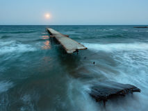 Night sea surf, ruined pier and Moon in sky (Black Sea, Bulgaria Royalty Free Stock Photos