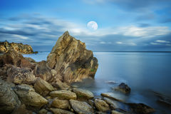 Night seascape with a full moon. A calm sea on a long exposure, a rocky desert beach. Moonlight night on the sea coast Stock Images