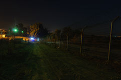Night security,  patrol car emerge. The night security patrol car is rolling along the fence and coming into view, illuminating with it's searchlight on the Royalty Free Stock Photo