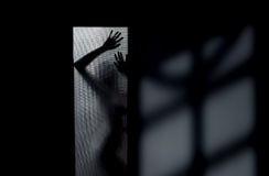 Night shadows. Silhouette of the sexy woman behind the glass door. Interior with deep shadows Stock Photos