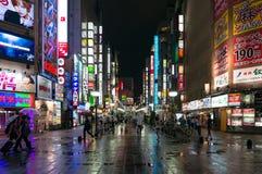 Night Shinjuku with people and bright advertising. Tokyo, Japan - August 29, 2016: Night Shinjuku with people and bright advertising. Text in Japanese advertises Stock Image