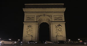 Night shot of Arc de Triomphe and car traffic in Paris. PARIS, FRANCE - SEPTEMBER 06, 2015: Low angle shot of car driving by Arc de Triomphe at night. Built in stock footage