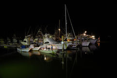 Night shot of a boat dock with two men talking. Night shot of several boats in a marina with two men talking about the day's catch Stock Photo