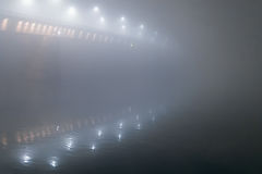 Night shot of a bridge in thick fog. Stock Images