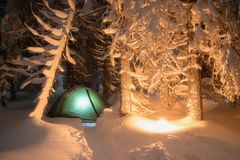 Night shot of burning fire, long exposure, sleeping in the snow outside. Night bivouac in the mountains. Christmas time. royalty free stock images