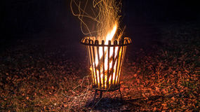 Night shot of a burning fire in a metal basket with leaves on the ground Stock Images