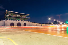 Night shot of Gwanghwamun gate of Gyeongbokgung Palace in Seoul, South Korea with taillights and headlights of cars in front of it Stock Photos