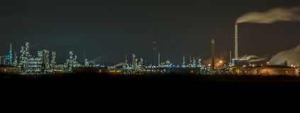 Huge power plant with many lights at night stock photography