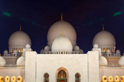 Night Shot of Illuminated Zayed Mosque in Abu Dhabi with White Marble Domes. Illuminated white marble facade and domes of Zayed Grand Mosque in Abu Dhabi of Royalty Free Stock Photos