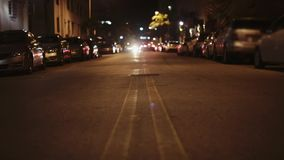Night shot from middle of a street. No traffic, bright light. stock video