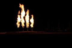 Night Shot of Quad Gas Flare. Four gas flares after a frack job in the Bakken. Waste gas is flared as a byproduct of oil production due to poor economic return Stock Images