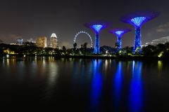 Night shot of Singapore skyline with Gardens by the Bay supertrees, Singapore Flyer and hotels reflected in water Stock Photo