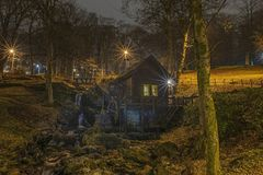 Night-shot of a small watermill in warm colors. stock photo