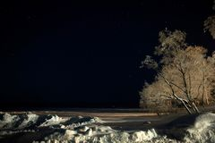 Night shot of the snowy shore of the lake. royalty free stock photos