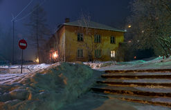 Night shot of street under snow with old residential house in wi Royalty Free Stock Images