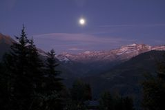 Night shot of Swiss Mountains. Night Shot of the Swiss Mountains at Leysin, with the moon over the mountain tops Stock Photo