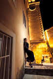 Night shot of woman leaning against old building at street Royalty Free Stock Photos