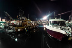 Night shot of wooden and motorboats moored at sea port Stock Photo