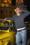 Night shot of young man standing next to small car Stock Image