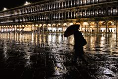 Night silhouette of woman with umbrella on a rainy night in Saint Mark`s Square in Venice with golden light royalty free stock photos