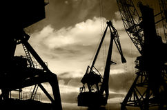 Night silhouettes of cargo cranes in the sea port black & white photo Royalty Free Stock Photo