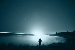 Night sky above lake with man's silhouette Stock Photo