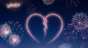 Night sky with fireworks shaped as a broken heart.series. A dark night sky with a sparkling red firecracker in the shape of a broken heart composed into.series Stock Image