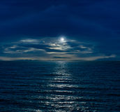 Night sky with full moon. And reflection in sea and clouds Stock Image