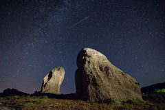 Night sky landscape with a  meteor and two menhirs Royalty Free Stock Photo