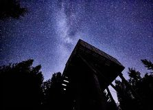 Night sky with the Milky Way over the forest and a bird-watching tower. Trees surrounding the scene royalty free stock photos