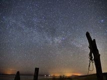 Night sky and milky way stars, Cygnus constellation over sea royalty free stock photography