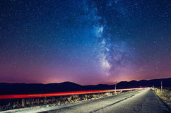 Night sky with milky way and stars. Night road illuminated by ca Royalty Free Stock Photography